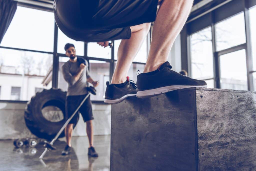a man in a gym doing box jumps and wearing cross training shoes. a decorative image in an article about how to choose the right athletic shoes for any workout.