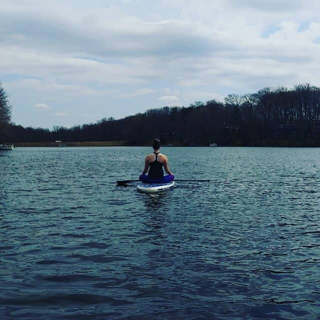 Woman sitting on a paddle board, Empower Your Wellness blog.