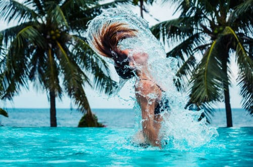 A Sexy Young Woman Is Doing A Hairflip And Creating Splashes In A Swimming Pool With Palm Trees And The Ocean In The Background