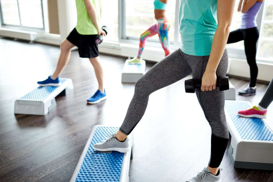 Fitness Sport Aerobics And People Concept Group Of Smiling People Working Out With Dumbbells Flexing Muscles On Step Platforms In Gym