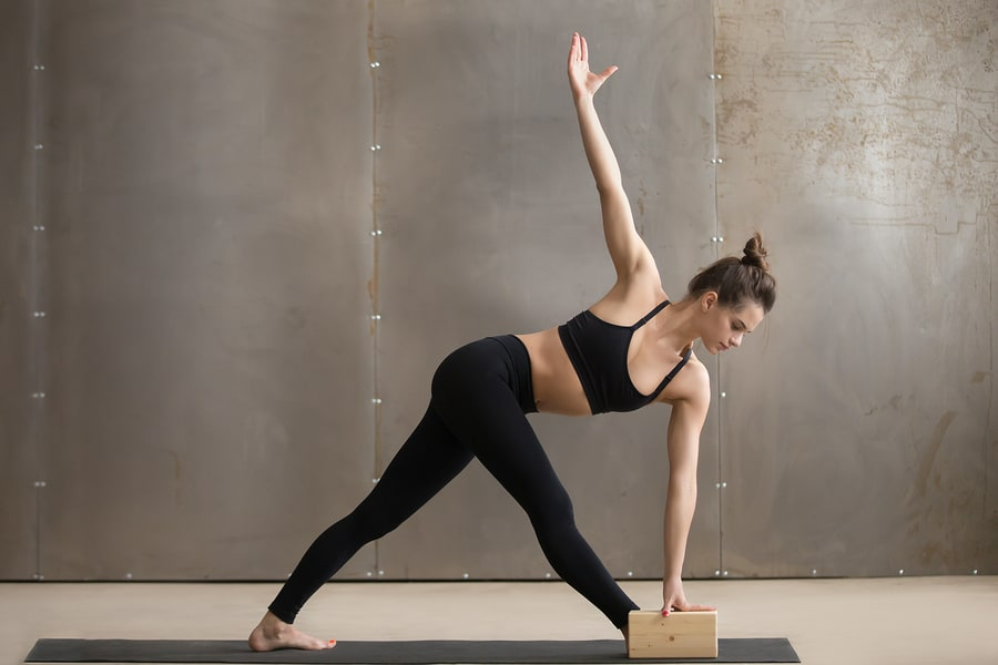 A girl practicing yoga using a block demonstrating exercise modifications.