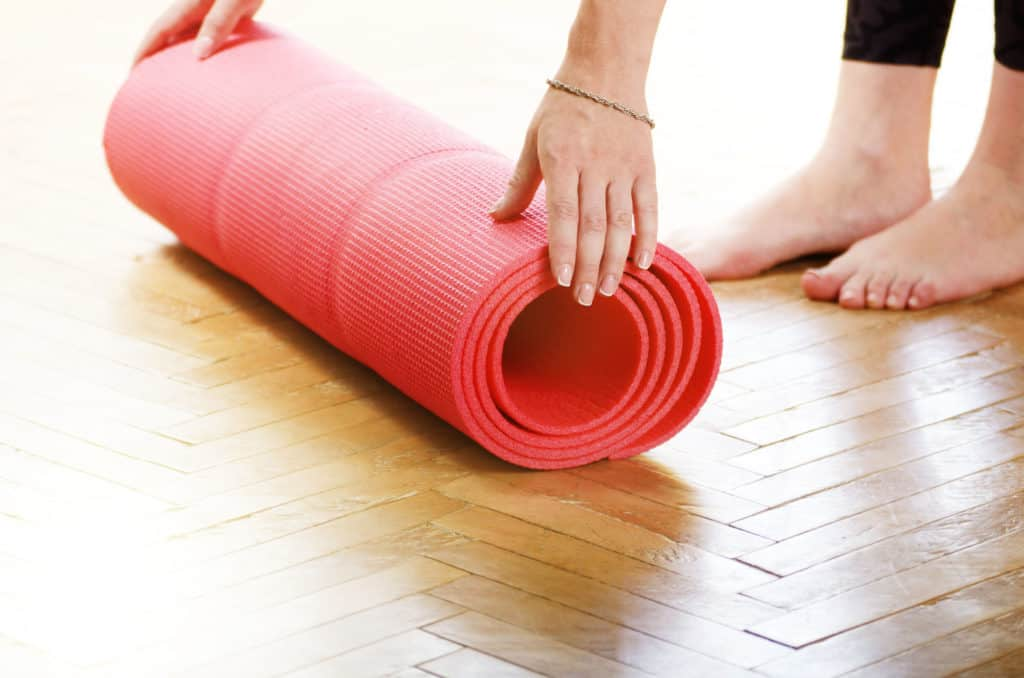 Female Hands Unrolling Yoga Mat Before group fitness class