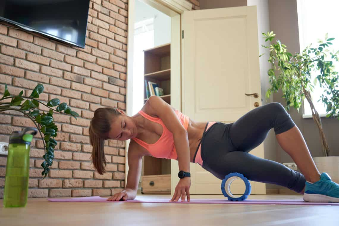 woman at home using a foam roller in her living room
