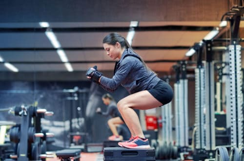 Fitness Sport Exercising And People Concept Woman Doing Squats On Platform In Gym Woman Doing Squats On Platform In Gym