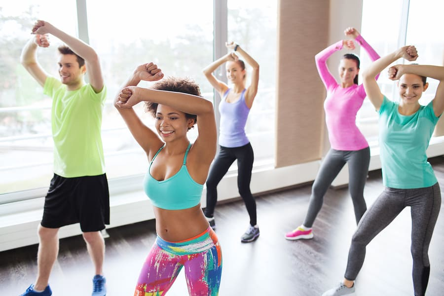 fitness, sport, dance and lifestyle concept - group of smiling people with coach dancing zumba in gym or studio body awareness with exercise.