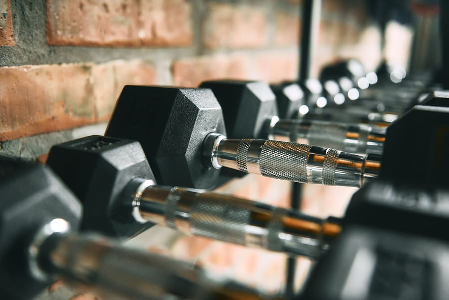 dumbbell rack against a brick wall at a gym