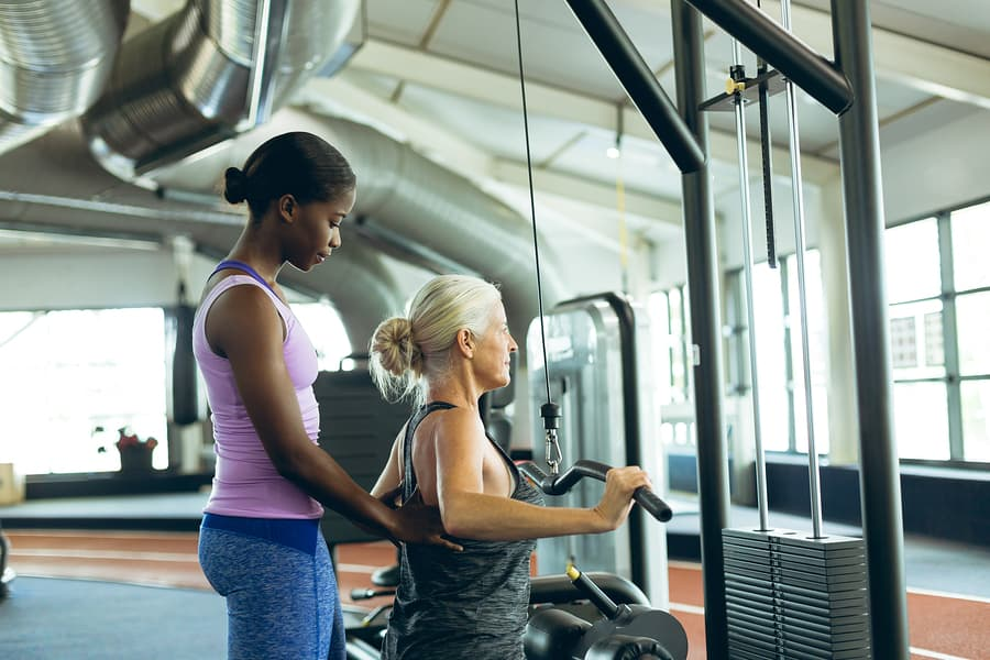 a trainer assisting an older woman on the lat pulldown machine