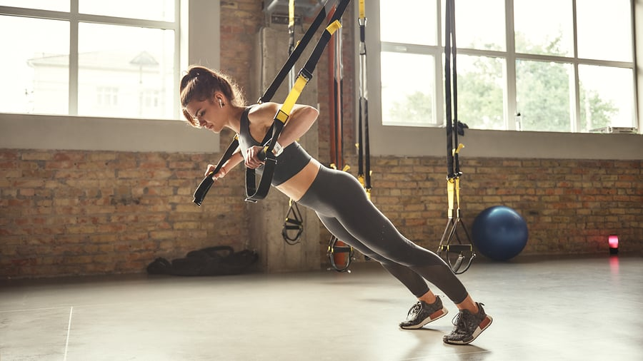 woman using a trx space saving home exercise equipment