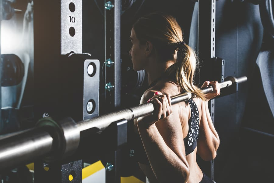 Young woman using strength training equipment barbell at gym