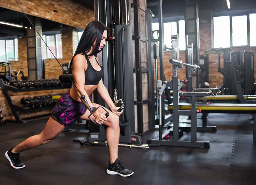 Young brunette fit woman execute exercise with exercise machine Cable Crossover in gym. Strength training equipment.