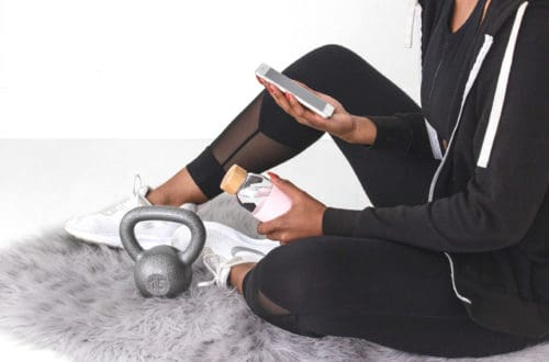 woman exercising evaluating health and fitness information on her phone