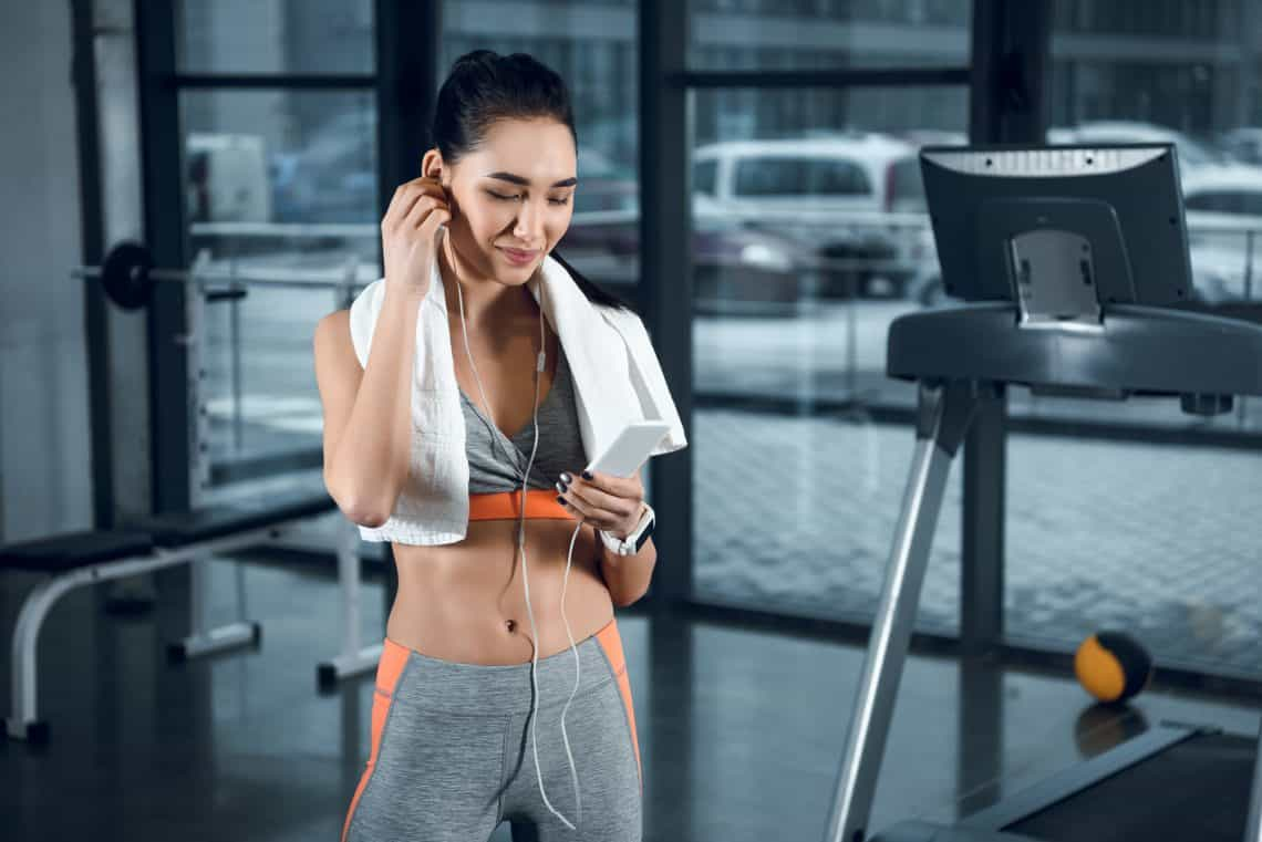 woman at the gym reading fitness information on her phone