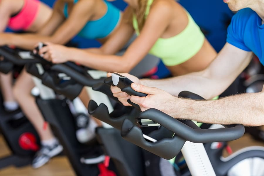 people riding a spin bike in a spin class