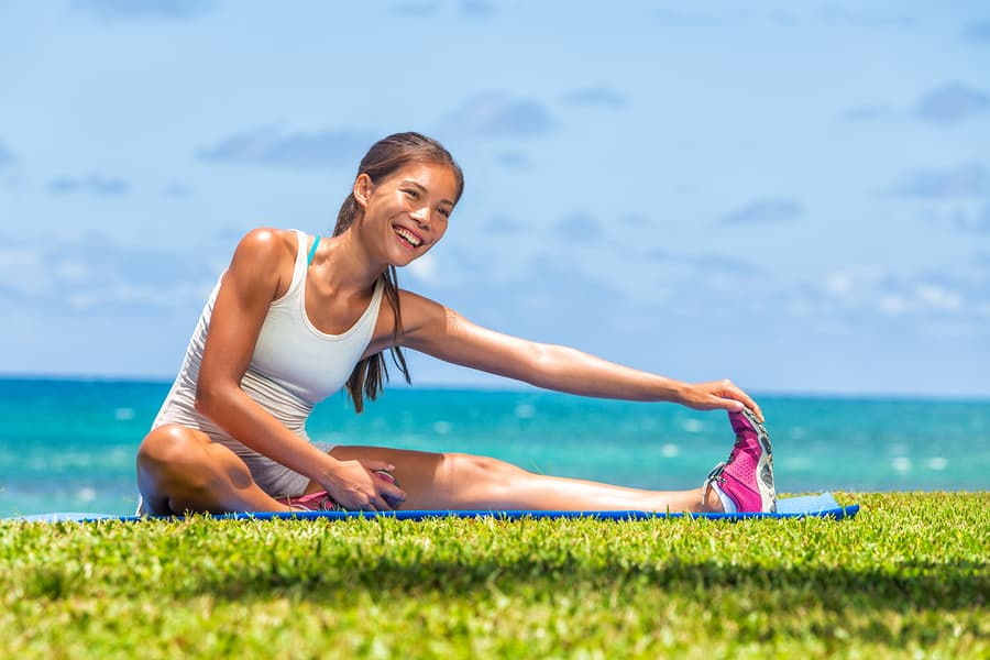 woman stretching outside on a yoga mat sunny day home workout