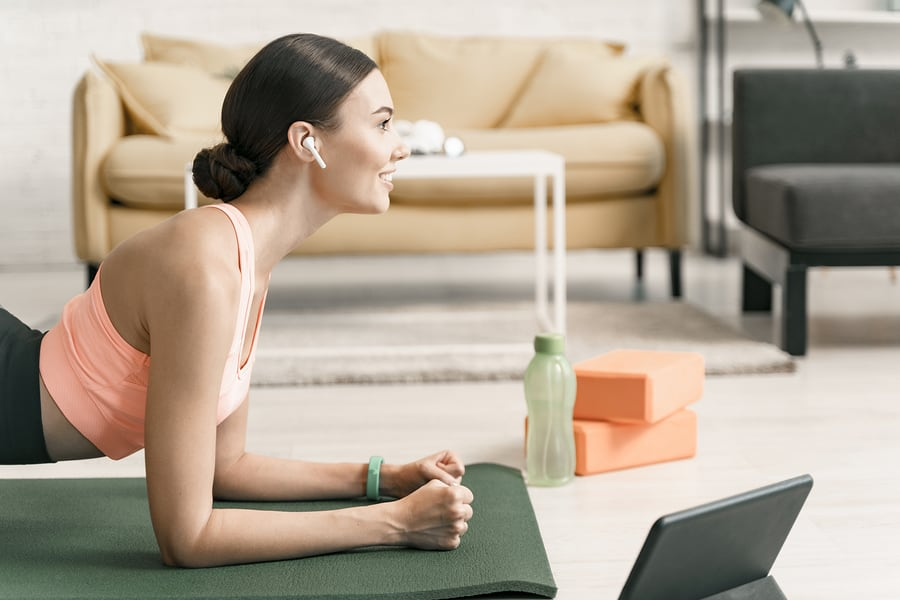 Woman planking on a mat, home workout next to a tablet.