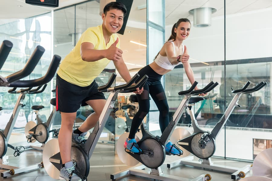 Young cheerful couple showing thumbs up while looking at camera during indoor cycling at the gym. Use good form to prevent cycle class injuries.