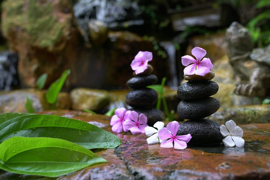 Stack of zen stones and flowers in a garden with waterfall. Stress management activities.