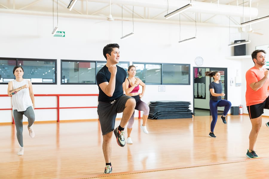group fitness class performing an interval training workout as a decorative image in an article explaining the difference between tabata vs. hiit