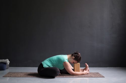 woman in seated half forward fold using a yoga block