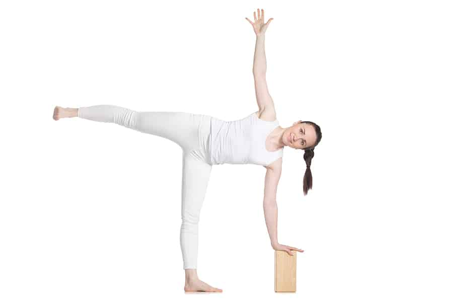 woman performing half-moon yoga pose with a yoga block demonstrating how to use yoga blocks for injury prevention.