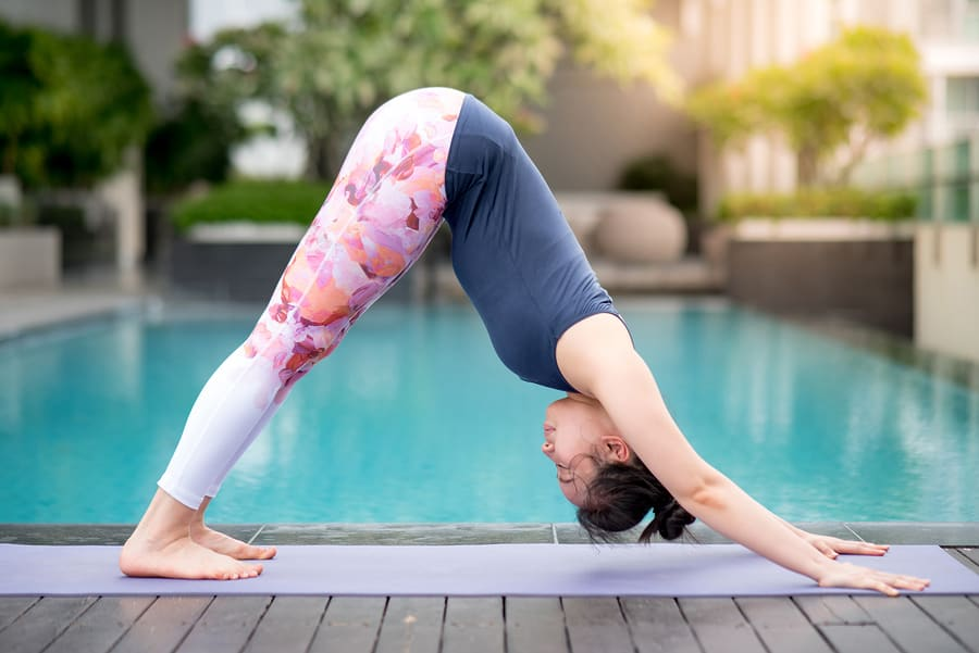 woman by a pool doing downward dog pose on a purple yoga mat.