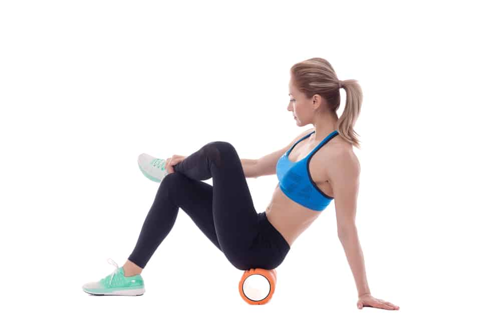 woman using a foam roller to roll out glutes