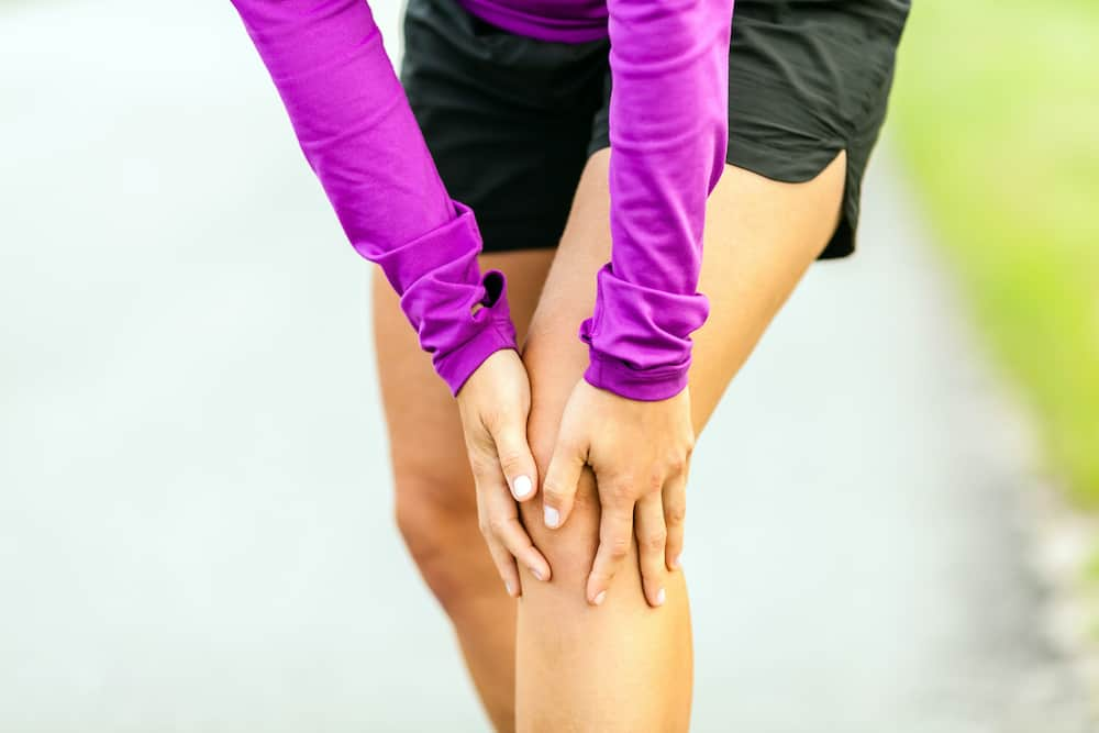 fitness woman clutching knee in pain