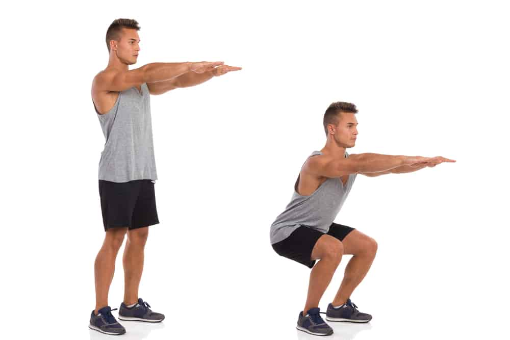 man demonstrating proper squat form to protect the lower back