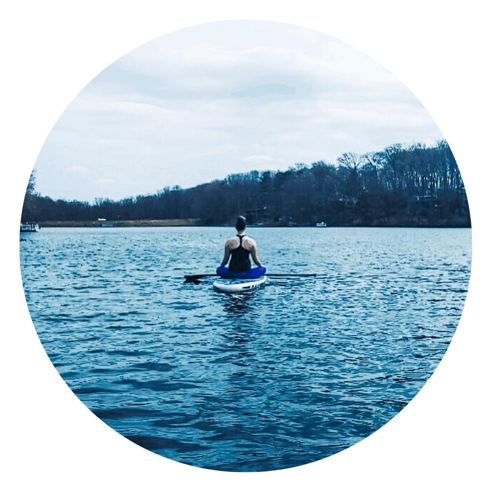 woman sitting on a paddleboard on a lake