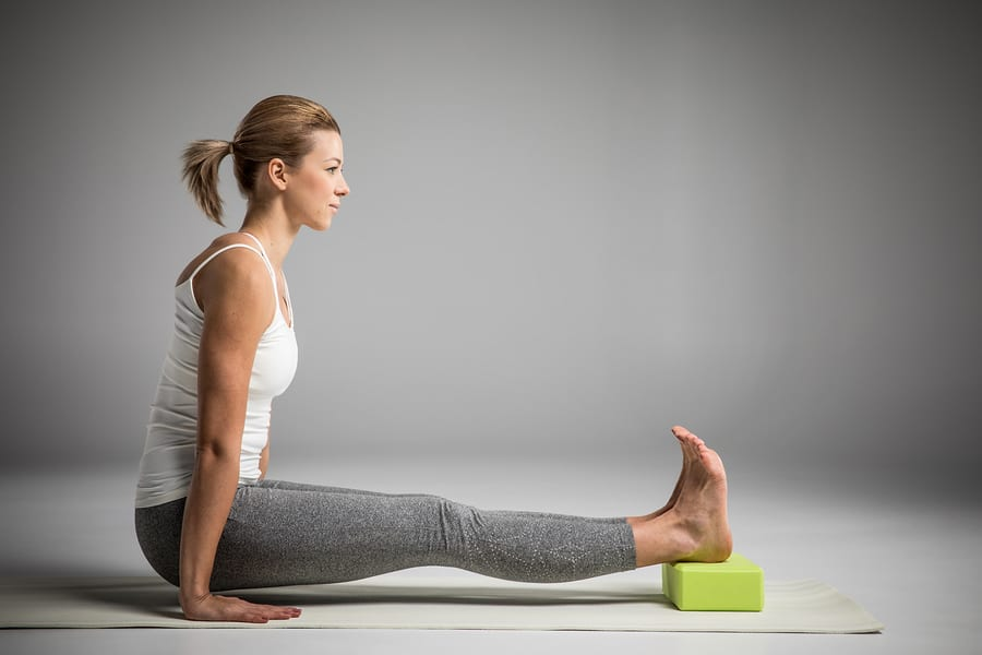 woman practicing yoga with a block for injury prevention.
