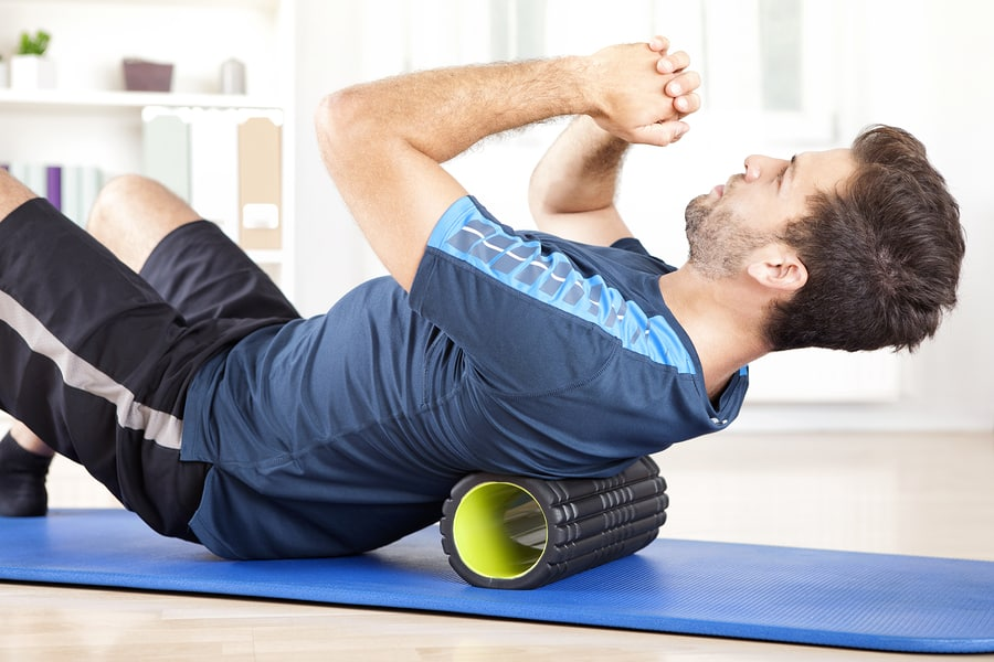 man performing thoracic extension over a foam roller for posture exercises