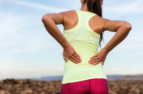 woman runner holding lower back in pain staying active with lower back pain