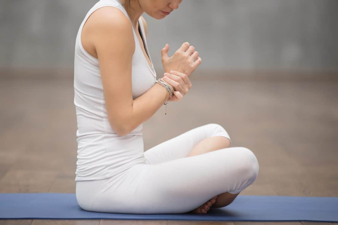 woman holding her wrist demonstrating wrist pain with yoga