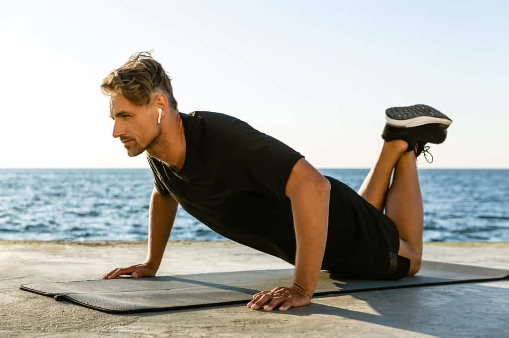 man doing push ups on his knees demonstrating exercise modifications for wrist pain.