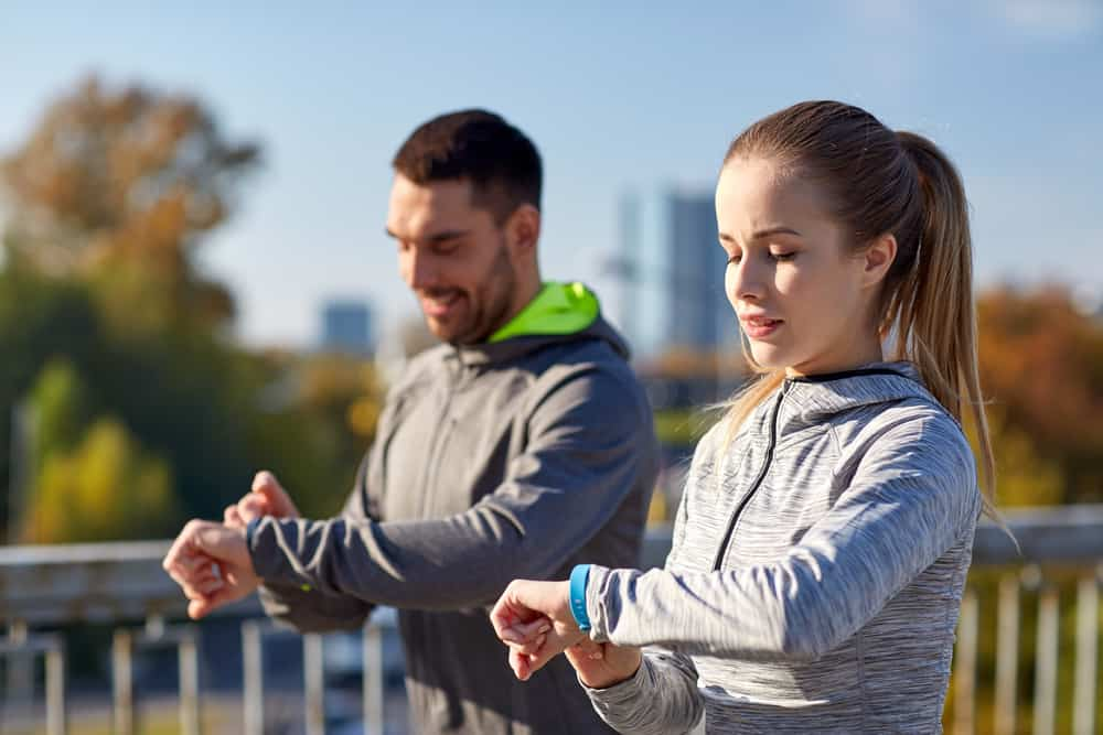 couple running outdoors using fitness trackers or fitness watches