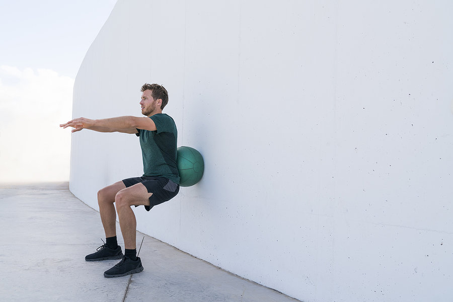 man doing wall ball squats as part of a low impact workout