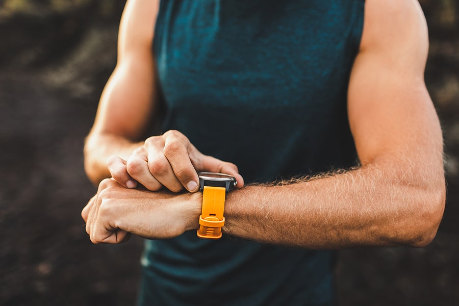 man working out looking at his fitness tracker, a decorative image in an article about gifts for fitness lovers.