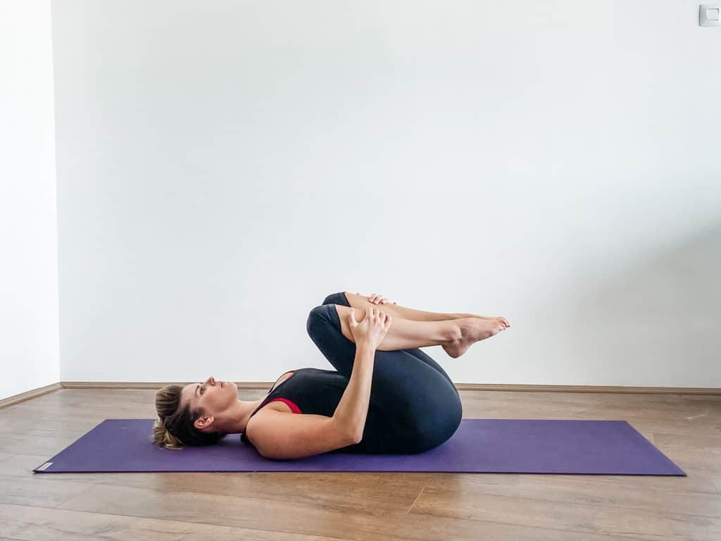 Woman on a yoga mat performing lower back stretch double knee to chest