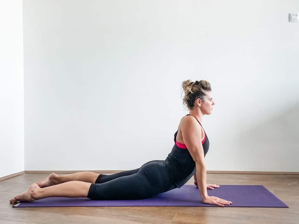 woman doing cobra pose, prone press up for spinal flexibility