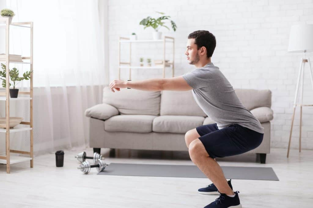 man workout out at home using exercise equipment for small spaces.