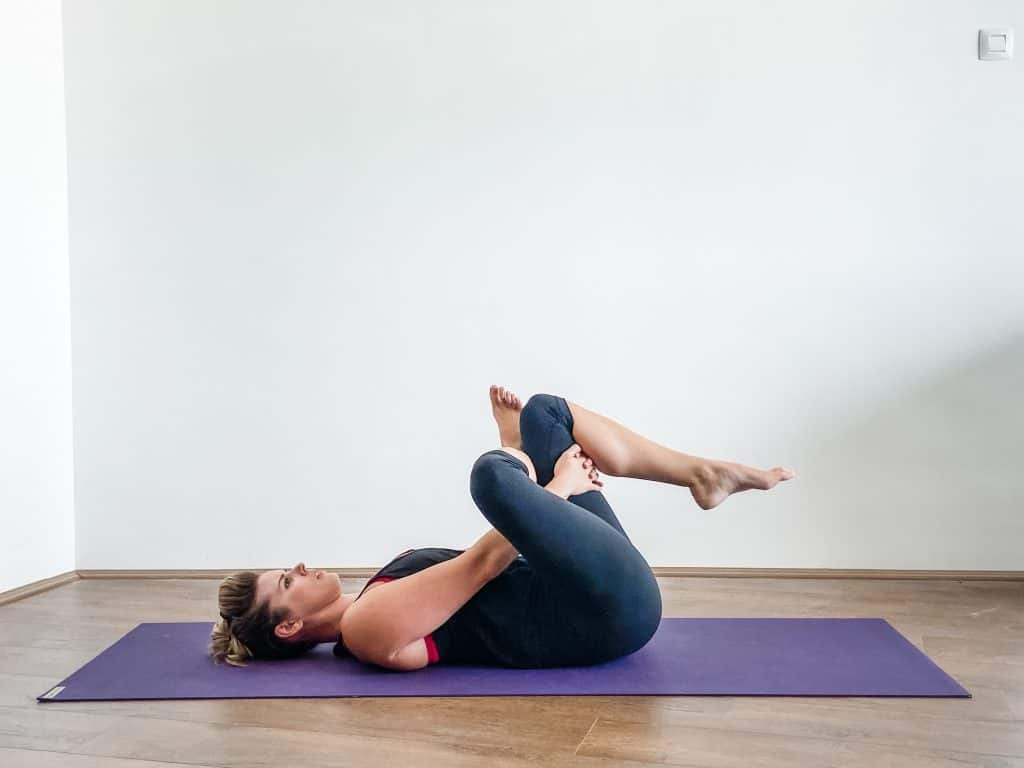 woman on a yoga mat demonstrating a figure 4 stretch, stretches to help IT Band syndrome