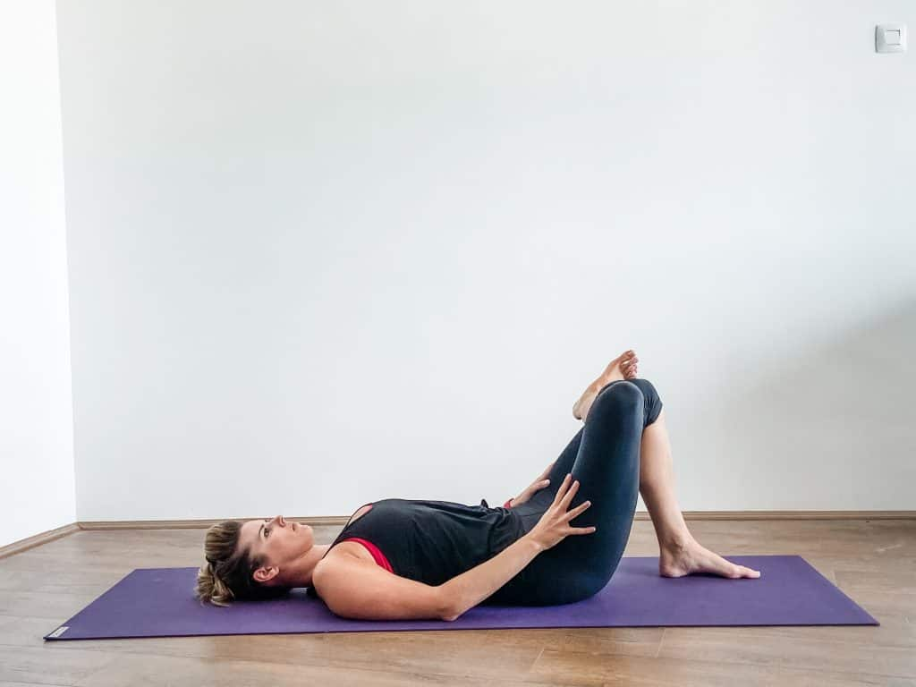 woman performing a supine figure 4 stretch on a yoga mat - hip flexibility exercises