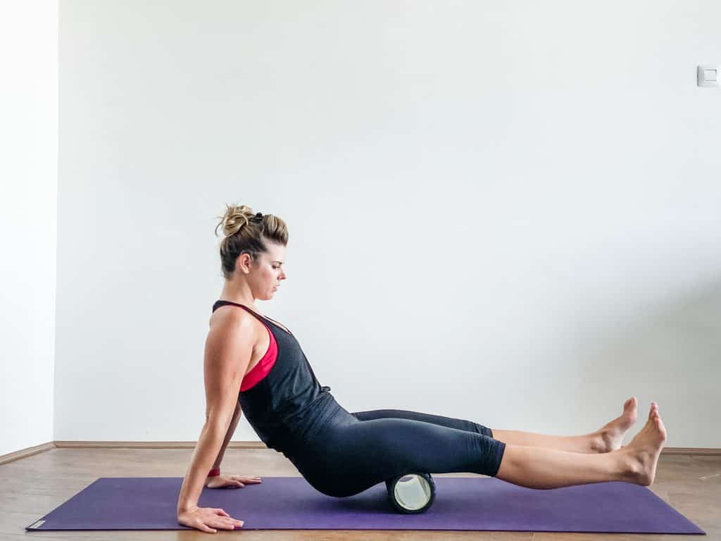 woman using foam roller on hamstrings