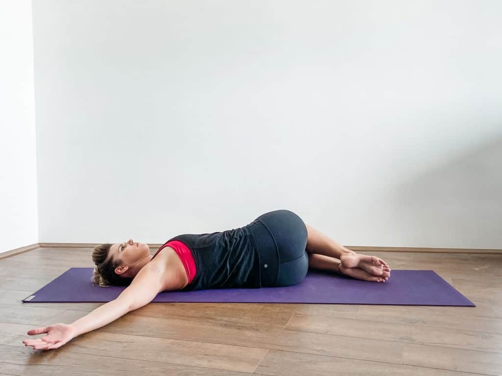 woman performing lower trunk rotation on a yoga mat - spine flexibility exericses