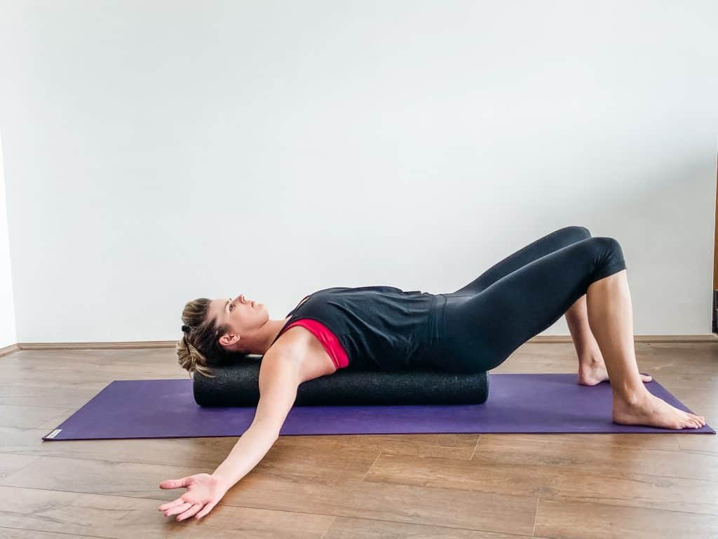 woman demonstrating pec stretch on foam roller