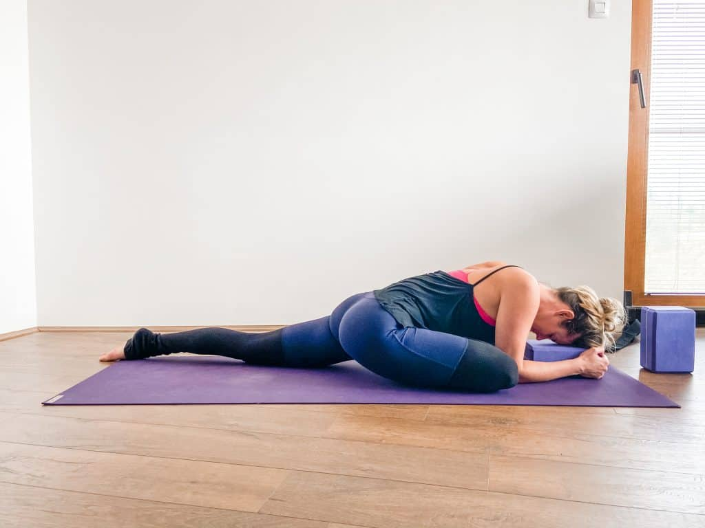 woman doing sleeping pigeon pose resting head on a yoga block - hip flexibility exercises