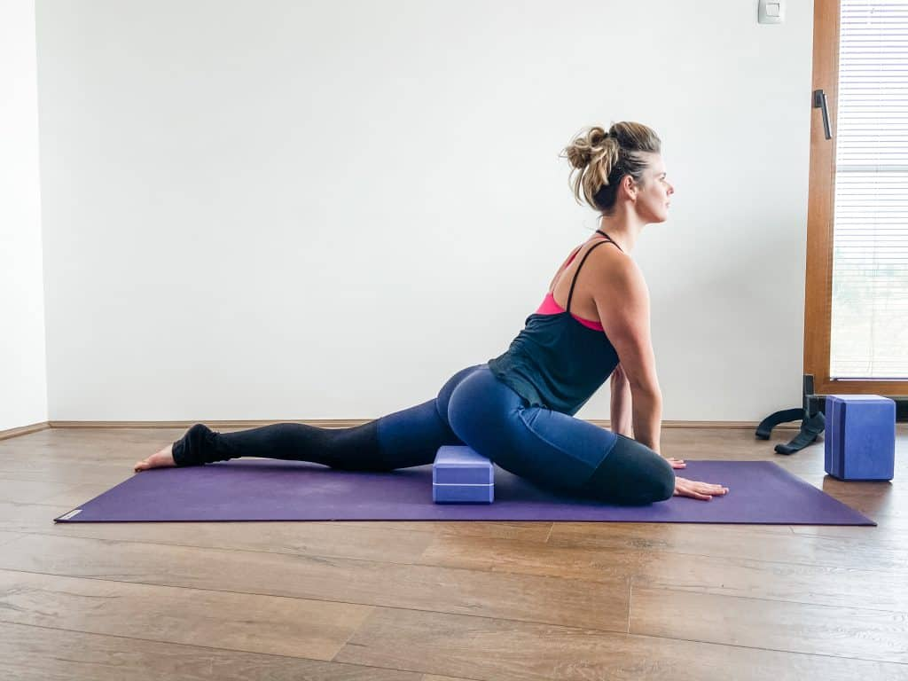 woman doing pigeon pose with a modification using a block under the hips - hip flexibility exercise