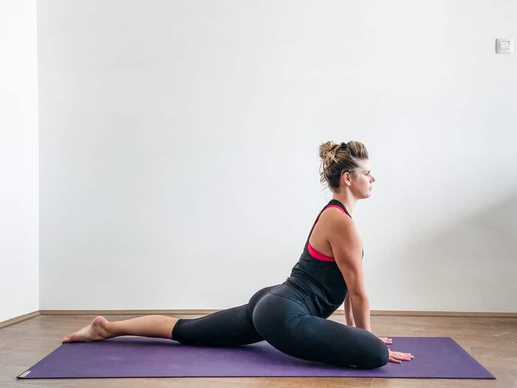 woman doing pigeon pose on a yoga mat for hip flexibility exercises