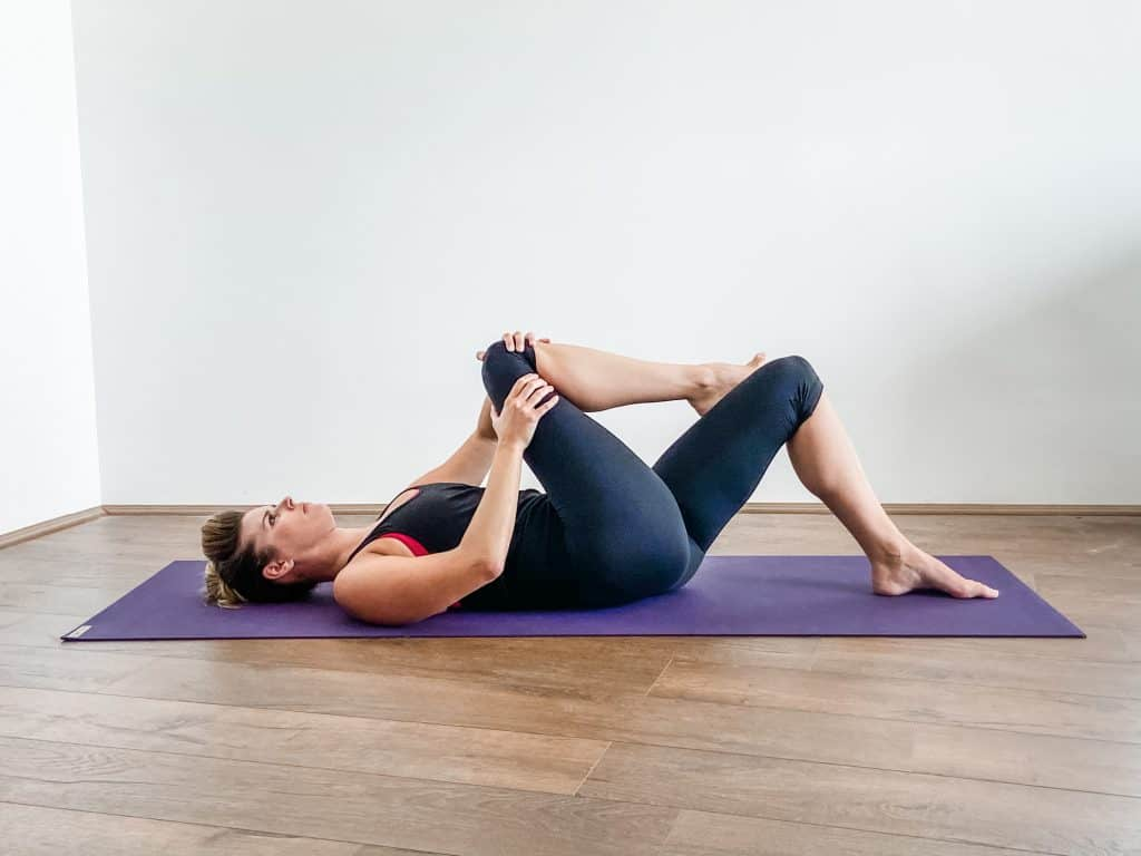 woman performing a supine piriformis stretch on a yoga mat - hip flexibility exercises