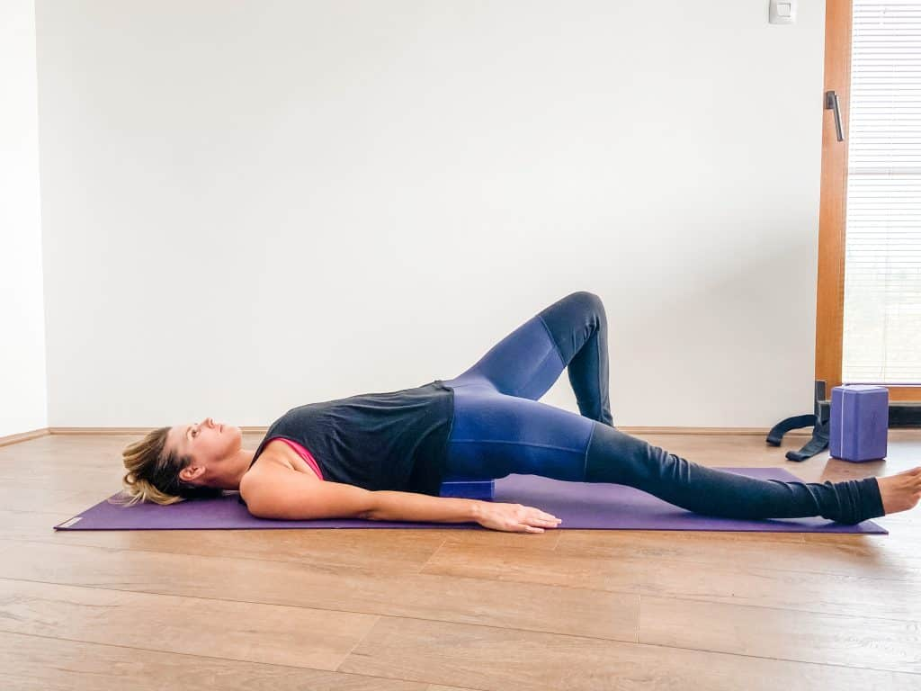 woman using a yoga block for supine psoas stretch - hip flexibility exercises